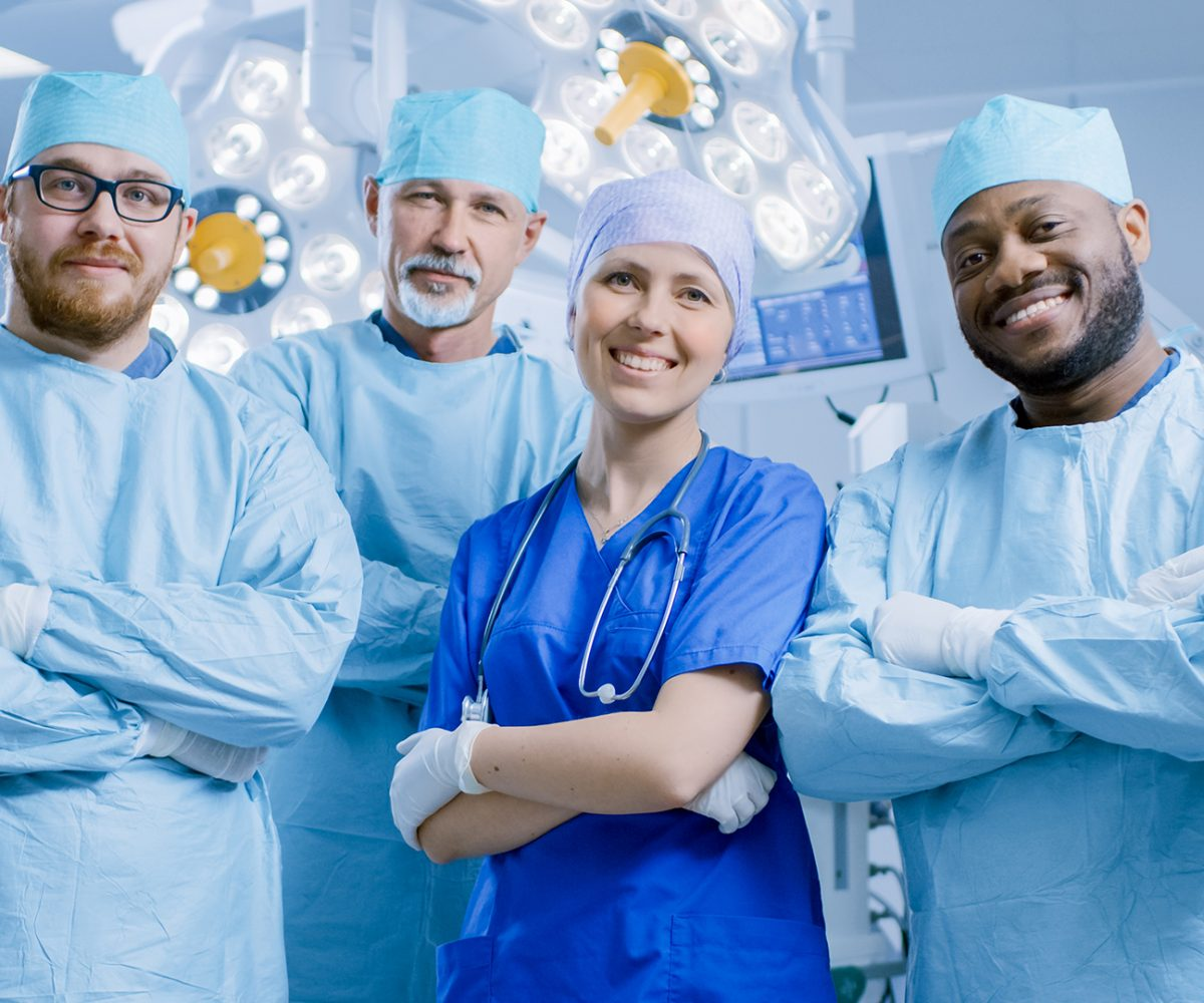 Diverse Team of Professional surgeon,  Assistants and Nurses Standing Proudly with Crossed Arms in the Real Modern Hospital with Authentic Equipment.