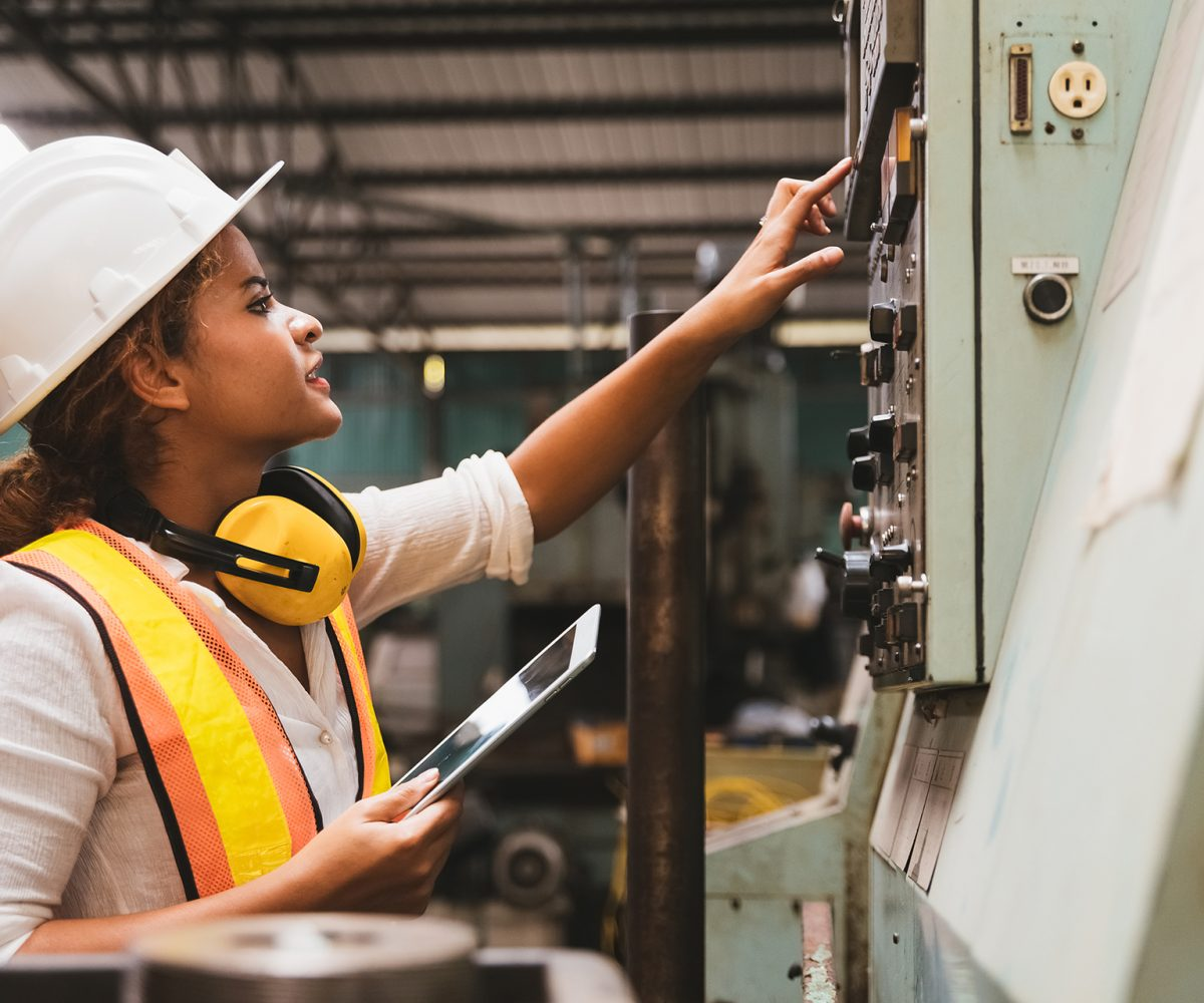 Industrial factory maintenance engineers woman inspect relay protection system of machinery and holding digital tablet with copy space. Industry, Maintenance, Engineering and construction concept.